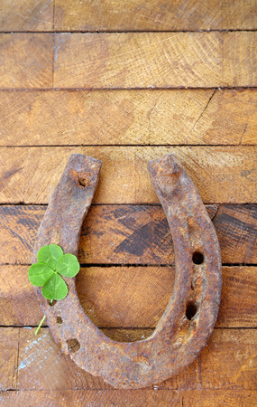 Old horse shoe,with clover leaf, on wooden background photo