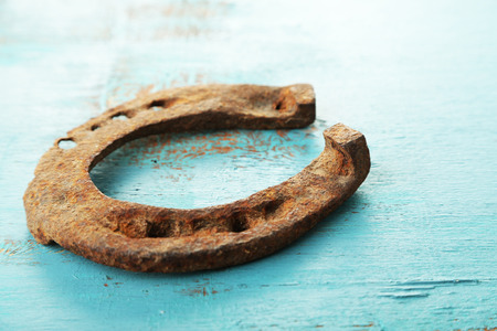 Old horse shoe on wooden background photo