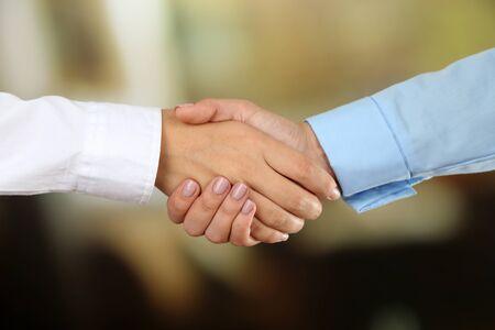 businessteam: Business handshake on bright background