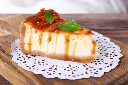 Cheese cake on paper napkin on cutting board on wooden table on light background