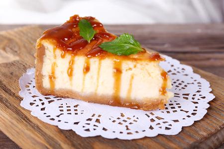 CAKE: Pastel de queso en la servilleta de papel en tabla para cortar en la mesa de madera sobre fondo claro