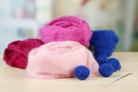 warmness: Wool for felting with needle on table on bright background