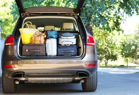 birretes: Maletas y bolsas en maletero del coche listo para partir para las vacaciones