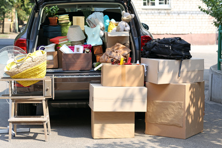 home moving: Moving boxes and suitcases in trunk of car, outdoors Stock Photo