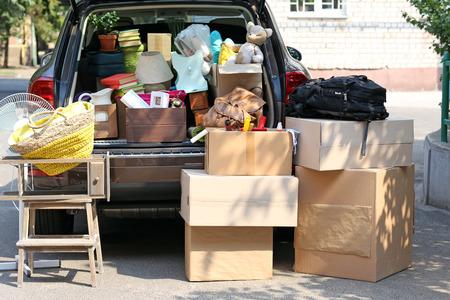 Umzugskartons und Koffer im Kofferraum des Autos, im Freien Lizenzfreie Bilder