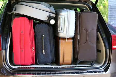 overburden: Suitcases and bags in trunk of car ready to depart for holidays