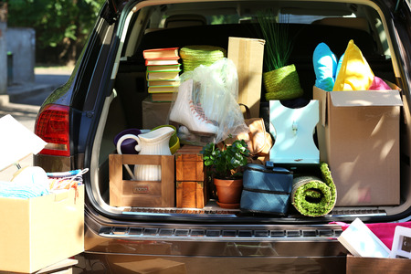 overburden: Moving boxes and suitcases in trunk of car, outdoors Stock Photo