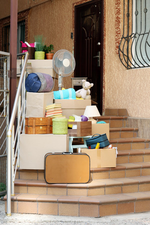 overburden: Moving boxes on stairs of new house, outdoors
