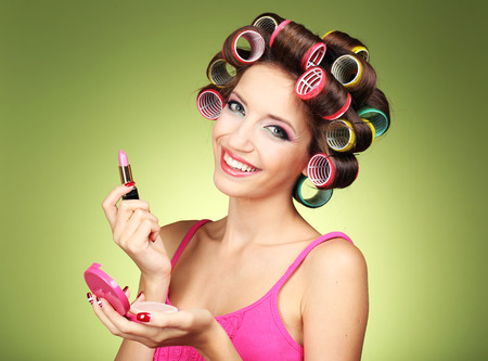 Beautiful girl in hair curlers on green background Stock Photo