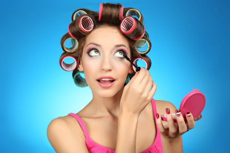 Beautiful girl in hair curlers on blue background Stock Photo