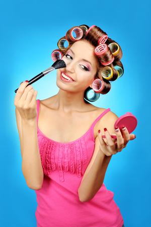 Beautiful girl in hair curlers on blue background Zdjęcie Seryjne