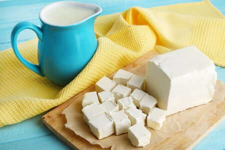 butterfat: Fresh butter on cutting board and jug with milk, on color wooden background