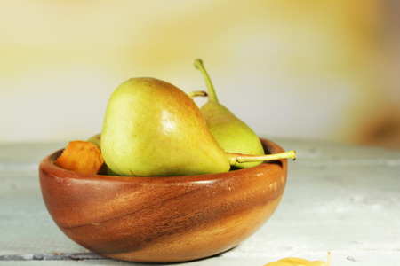 Ripe tasty pears in wooden bowl, on table, on nature background photo