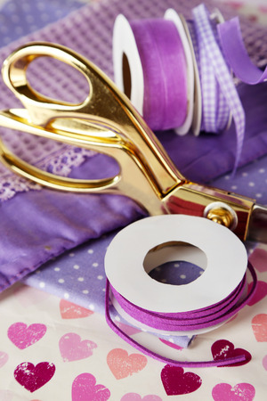 Ribbons with scissors and fabrics on bright background photo