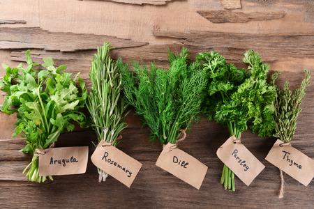Různé čerstvé bylinky na dřevěné pozadí Reklamní fotografie