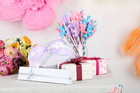 birthday present: Wedding or birthday gifts on decorated table, on bright background