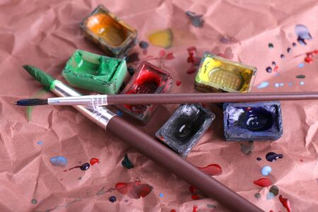 spilled paint: Watercolor paint cubes with brushes and spilled paint on brown paper background