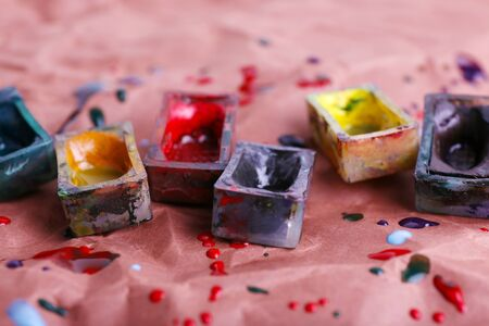 spilled paint: Watercolor paint cubes and spilled paint on brown paper background Stock Photo