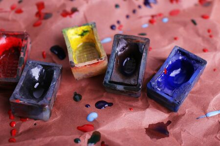 pintura derramada: Cubos de pintura de la acuarela y derramaron pintura sobre fondo de papel marr�n Foto de archivo