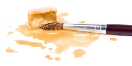 spilled paint: Watercolor paint cube with brush and spilled paint isolated on white Stock Photo