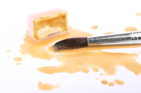 spilled: Watercolor paint cube with brush and spilled paint isolated on white Stock Photo
