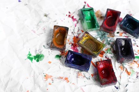 pintura derramada: Cubos de pintura de la acuarela y derramaron pintura sobre papel blanco de fondo Foto de archivo