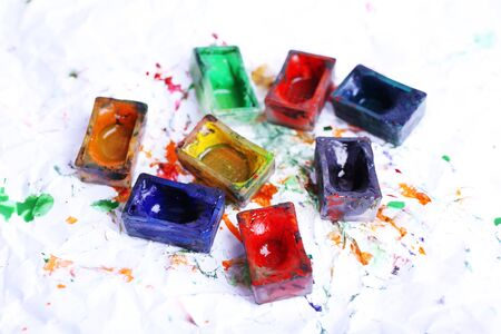spilled paint: Watercolor paint cubes and spilled paint on white paper background