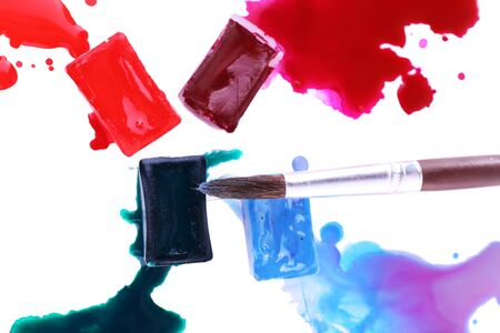 spilled paint: Watercolor paint cubes with brush and spilled paint isolated on white