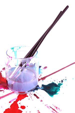 spilled: Brushes in glass jar with water and spilled paints isolated on white