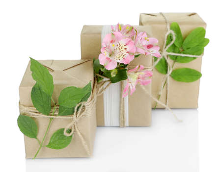 handcrafted: Natural style handcrafted gift boxes with fresh flowers and rustic twine, isolated on white Stock Photo