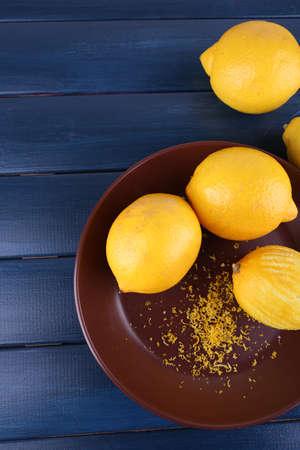 plato del buen comer: Limones en la placa sobre fondo oscuro de madera azul