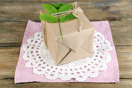 handcrafted: Natural style handcrafted gift box with fresh leaves and rustic twine, on napkin, on wooden background Stock Photo
