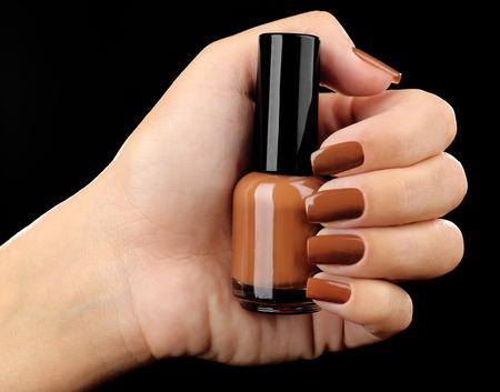 nail salon: Nail polish in hand, close-up