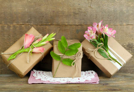 handcrafted: Natural style handcrafted gift boxes with fresh plants and rustic twine, on wooden Stock Photo