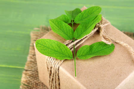 handcrafted: Natural style handcrafted gift box with fresh leaves and rustic twine, on wooden background