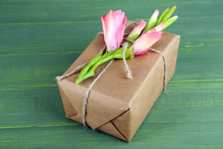 handcrafted: Natural style handcrafted gift box with fresh flowers and rustic twine, on wooden background