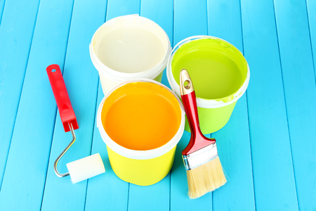 paintroller: Set for painting: paint pots, brushes, paint-roller on blue wooden table