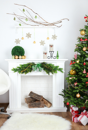 部屋の暖炉の近くのクリスマス ツリー 写真素材