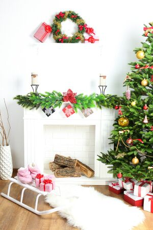 traditional christmas: Christmas tree near fireplace in room