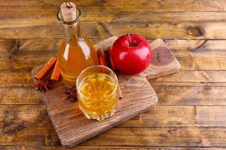 apple juice: Apple cider in glass bottle with cinnamon sticks and fresh apples on cutting board, on wooden background