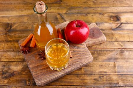 manzana: Sidra de manzana en botella de vidrio con palos de canela y manzanas frescas en la tabla de cortar, sobre fondo de madera
