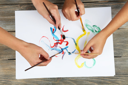kids hand: Two girls painting with paintbrush and colorful paints Stock Photo
