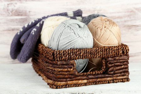 basket embroidery: Knitting yarn and mittens in basket, on wooden background Stock Photo