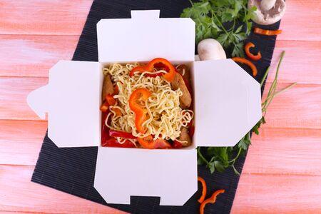 chinesisch essen: Chinesische Nudeln in Mitnehmerkasten auf schwarz Matte auf rosa Hintergrund