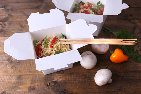 Chinese noodles in takeaway boxes with mushrooms and parsley on wooden background