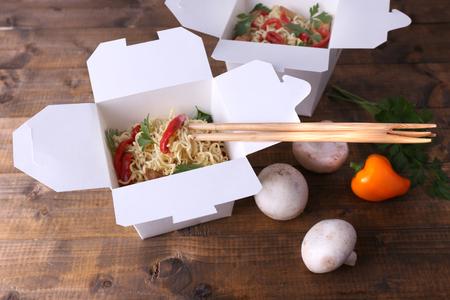 Nouilles chinoises dans des boîtes à emporter avec des champignons et persil sur fond de bois