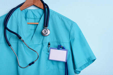 Doctor shirt with stethoscope on hanger on blue background