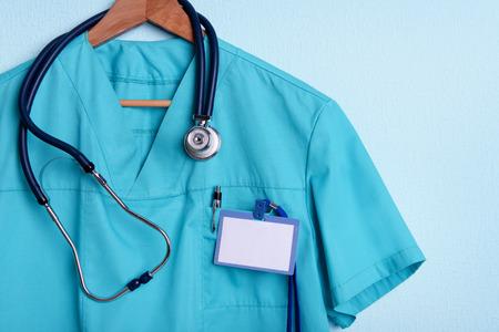 Doktor Shirt mit Stethoskop auf Kleiderbügel auf blauem Hintergrund