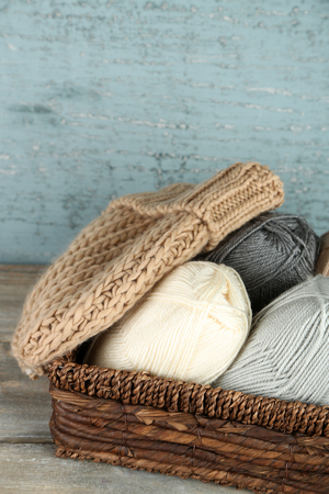 basket embroidery: Knitting yarn and cap in basket, on wooden background Stock Photo