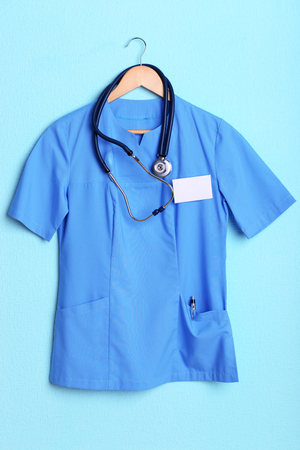 medical attendance: Doctor shirt with stethoscope on hanger on blue background